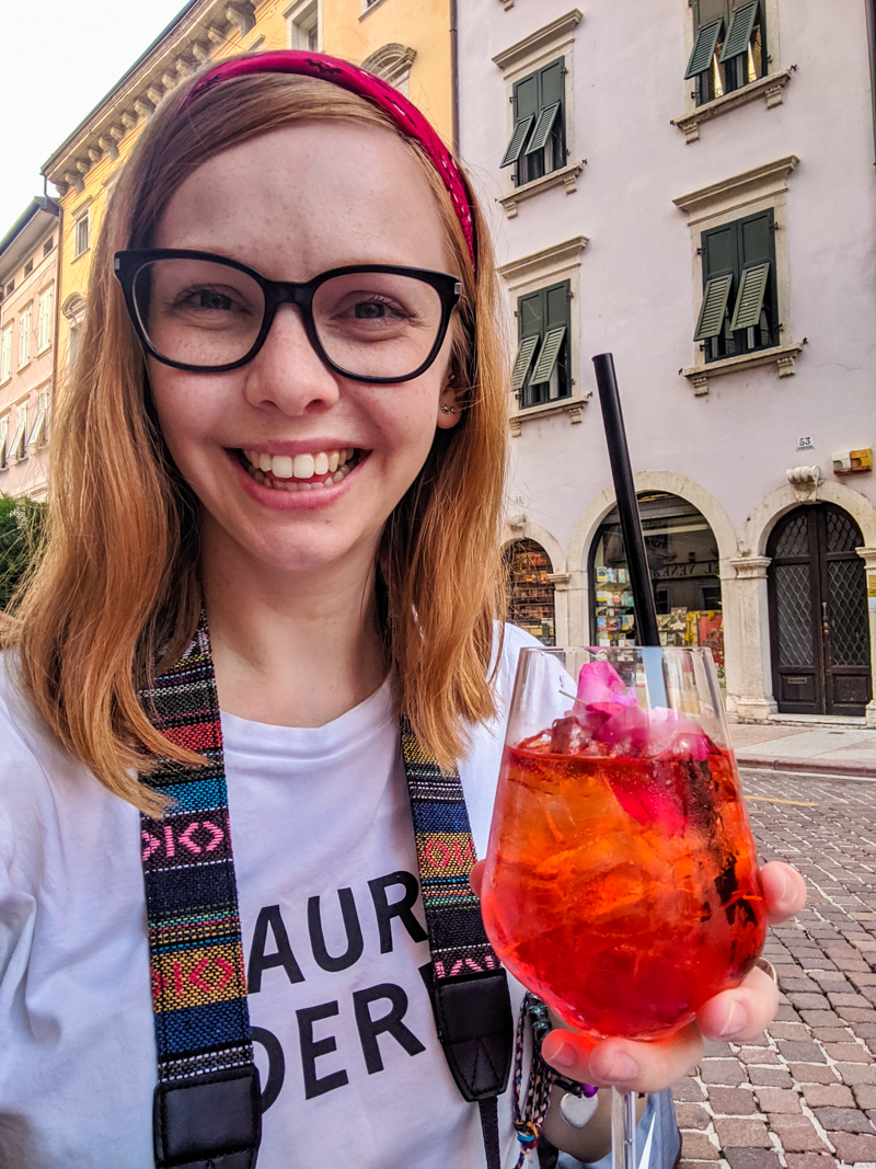 Almost Ginger blog owner drinking Aperol Spritz in Trento, Italy