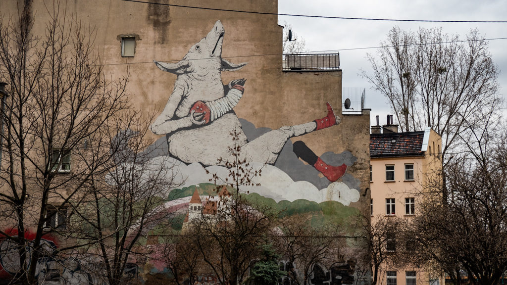 Large mural street art of a pig playing the accordian with human legs in Wrocław, Poland, how to spend 48 Hours in Wrocław, Poland