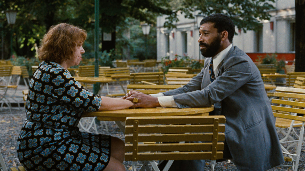 Film still from Ali: Fear Eats the Soul (1974) with two main characters sat at a table outside