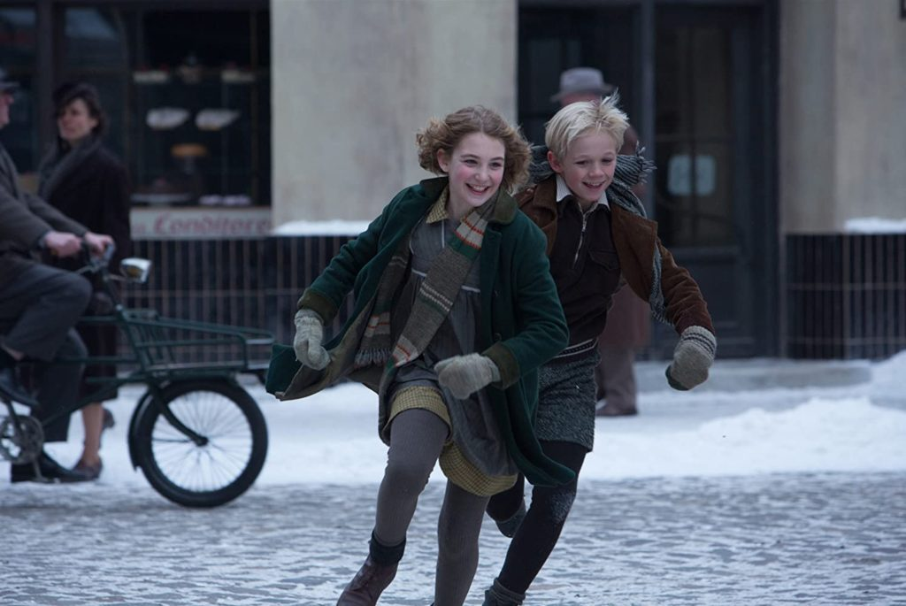 Film still from The Book Thief (2013) of two happy children running in a snowy town square