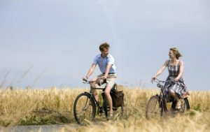 Film still from The Reader (2008), a movie set in Germany, of a young man and older woman cycling through the countryside