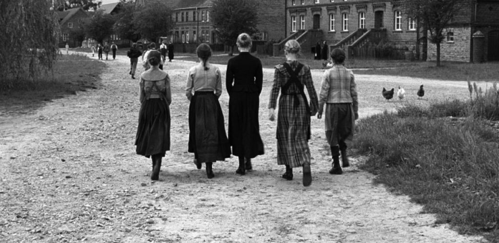 Black and white film still from The White Ribbon (2009) of children walking away