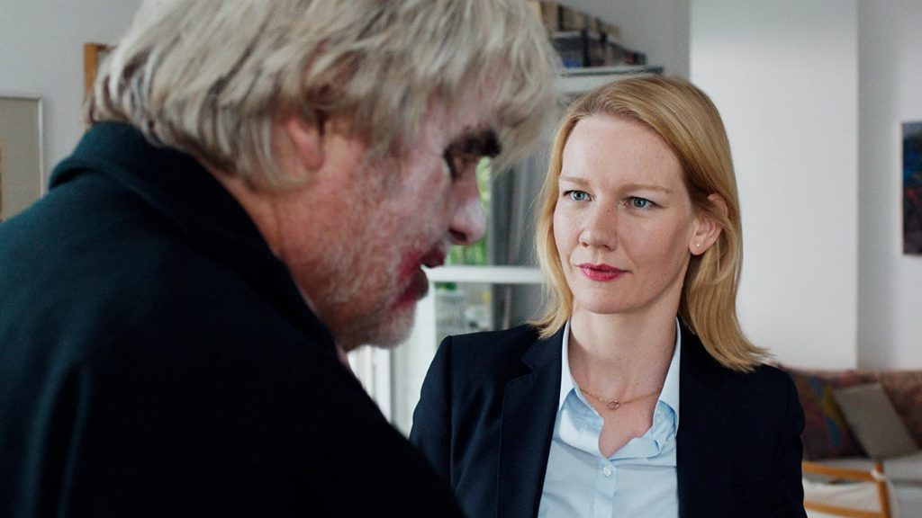 Film still from Toni Erdmann (2016) of a blonde woman and older man wearing clown makeup