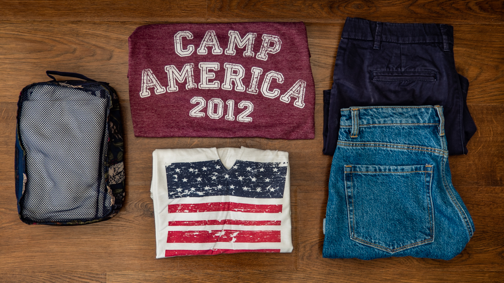 Flatlay of t-shirts in a packing cube, Camp America 2012 t-shirt, American flag t-shirt and two pairs of blue shorts