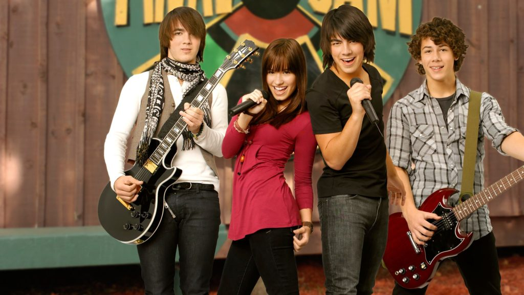 Camp Rock (2008) film still with The Jonas Brothers and Demi Lovato posing with instruments