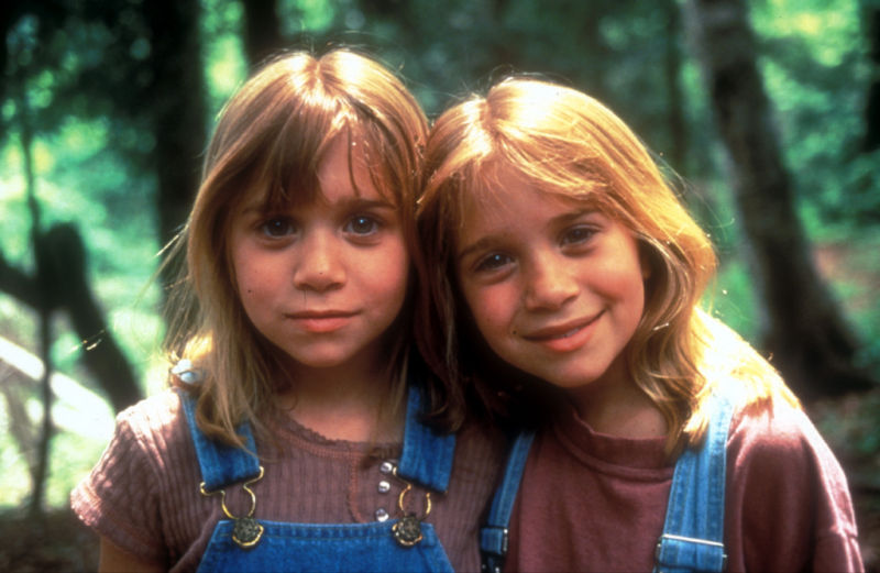 It Takes Two (1995) film still of Mary-Kate and Ashley Olsen smiling in dungarees