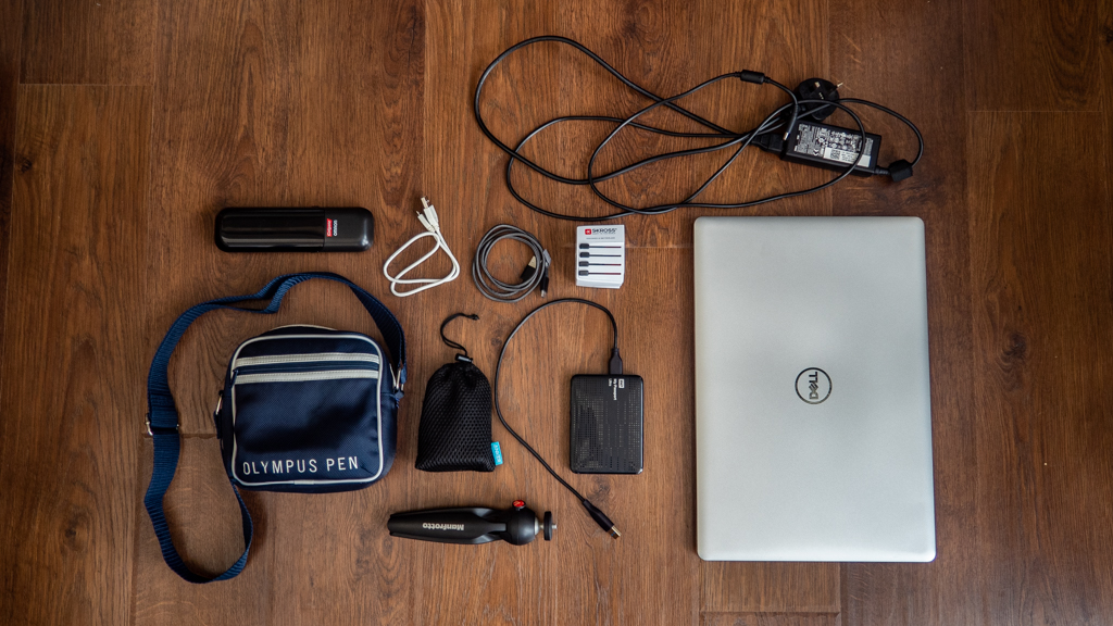 Flatlay of a camera, laptop and other technical gear camp counsellors should pack for summer camp