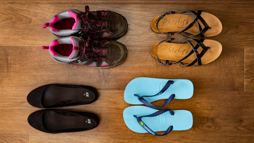 Flatlay of walking boots, black sandals, black ballet shoes and blue flipflops