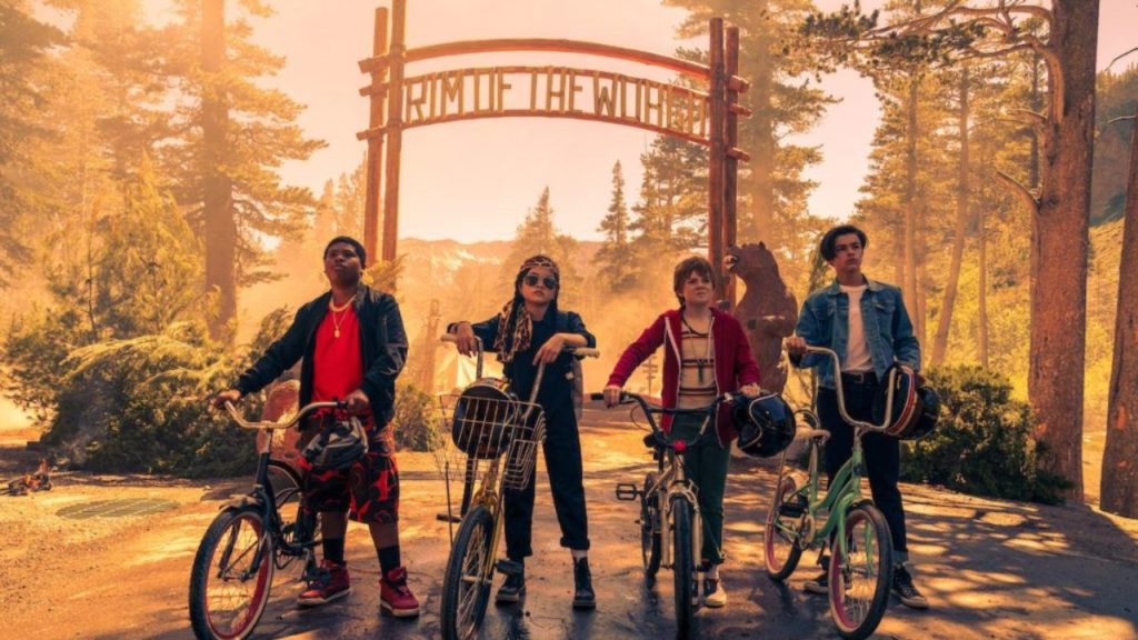 Rim of the World (2019) film still with four children on bikes outside the camp's sign