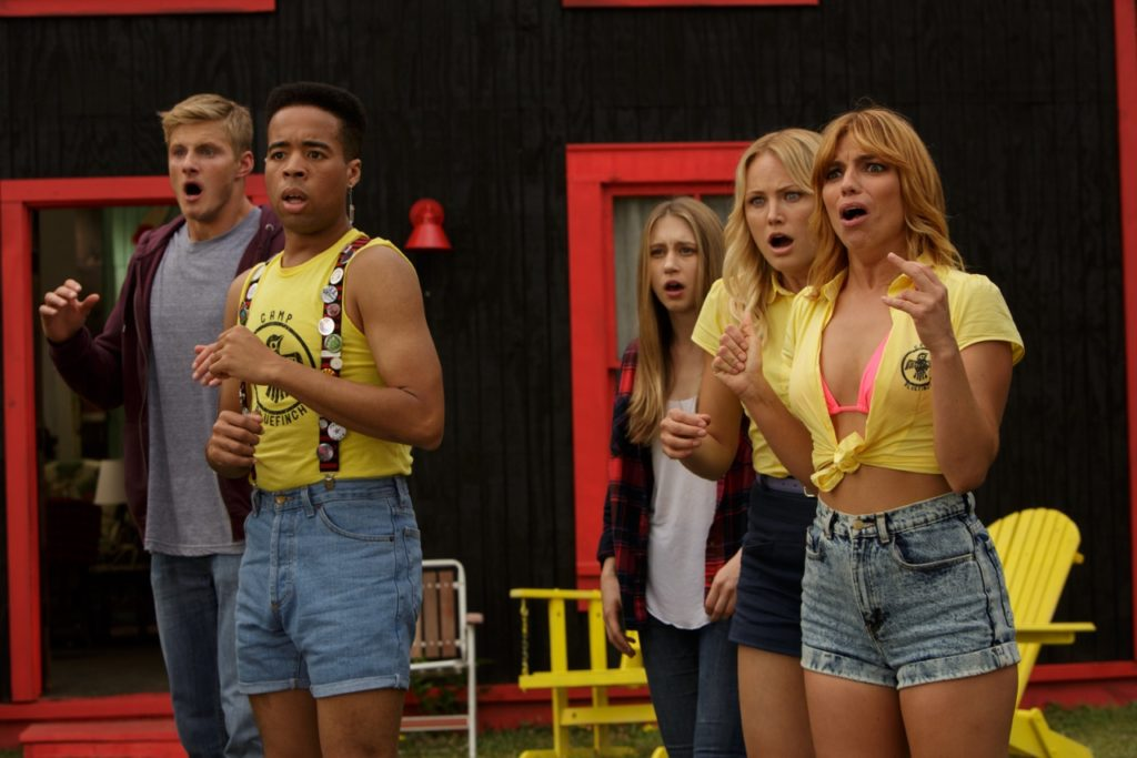 The Final Girls (2015) film still featuring five summer camp counsellors in uniform looking horrified