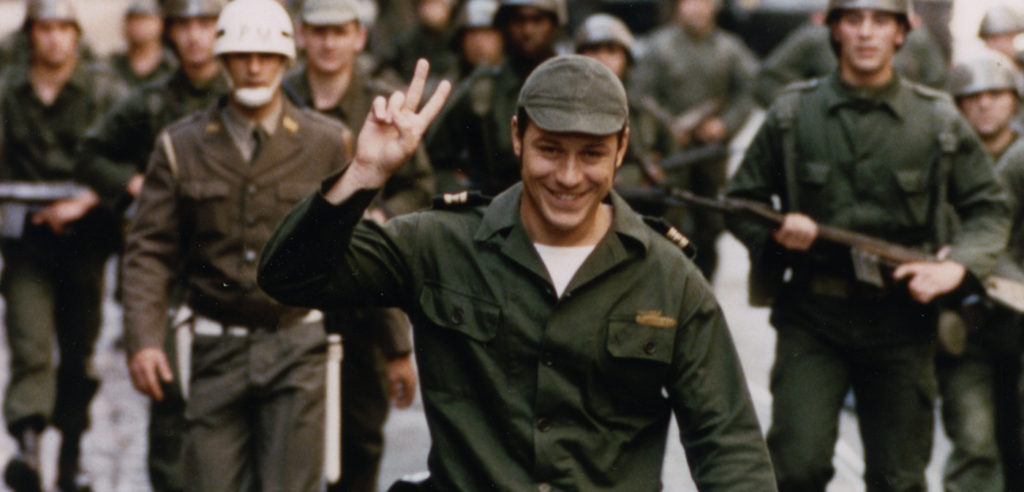 Still of a military man doing the peace sign from the Portuguese film April Captains (2000)