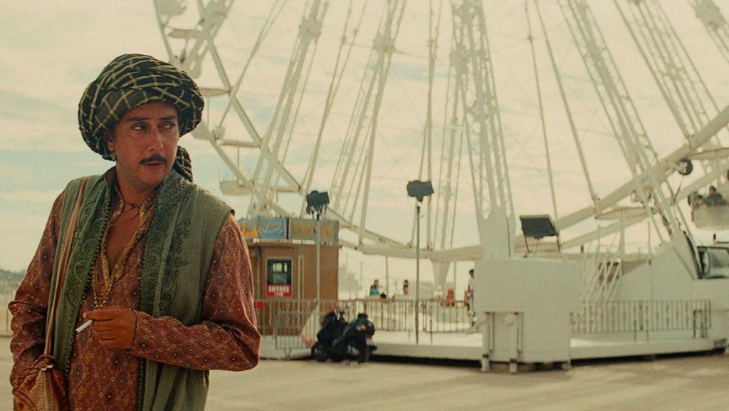Still of a fantastican Arabian man next to a Ferris Wheel from the Portuguese movie Arabian Nights (2015)