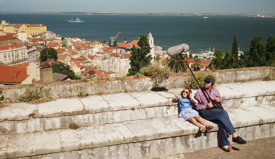 Still of a male filmmaker and small girl with a view of Lisbon from the movie Lisbon Story (1994)