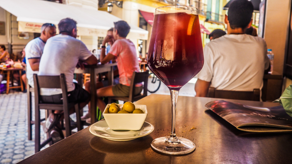 Tinto de Verano cocktail with olive bowl outside a bar in Málaga, Spain