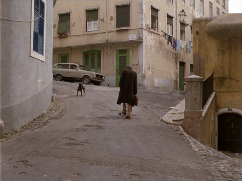 Still of a man walking up a hill in Lisbon in a rundown neighbourhood from the Portuguese film Recollections of the Yellow House (1989)